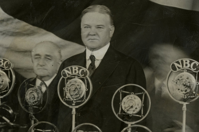 President Hoover standing before the microphones at the annual meeting of The Associated Press at the Waldorf Astoria Hotel, 04/22/1929. Here he delivered his first public address since the inauguration.